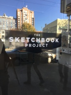 "Photo of door to the Brooklyn Art Library showing the name of the project ""The Sketchbook Project"" as well as reflections of the buildings and people in front of the door."